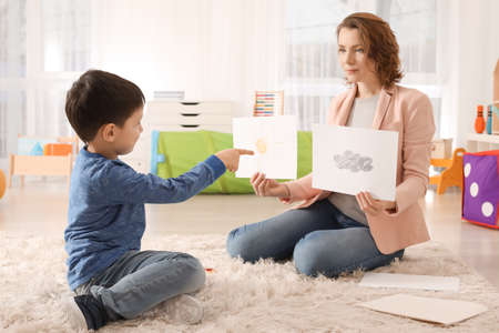Foto de Female psychologist working with boy suffering from autistic disorder - Imagen libre de derechos