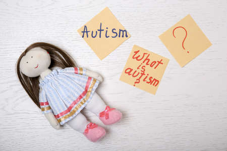 Foto de Notes with words related to autism and doll on light background, top view - Imagen libre de derechos