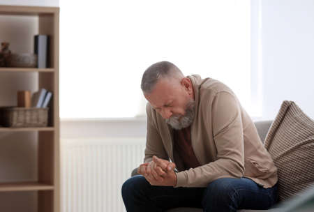 Foto de Depressed senior man sitting on sofa indoors - Imagen libre de derechos