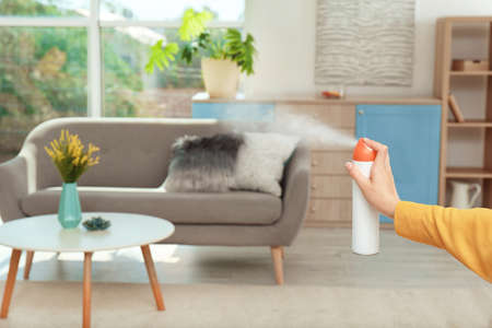 Photo for Woman spraying air freshener at home - Royalty Free Image