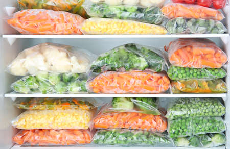 Foto de Plastic bags with deep frozen vegetables in refrigerator - Imagen libre de derechos