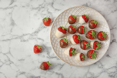 Foto de Flat lay composition with chocolate covered strawberries on marble background - Imagen libre de derechos