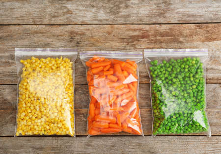 Foto de Plastic bags with frozen vegetables on wooden background, top view - Imagen libre de derechos