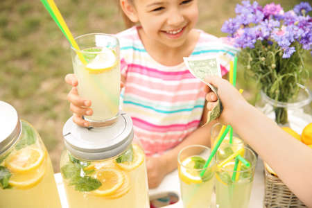 Photo for Little girl selling natural lemonade at stand in park - Royalty Free Image