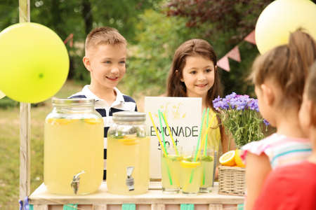 Photo for Little kids selling natural lemonade at stand in park - Royalty Free Image