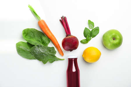 Photo pour Glass bottle of fresh juice and ingredients on white background, top view - image libre de droit