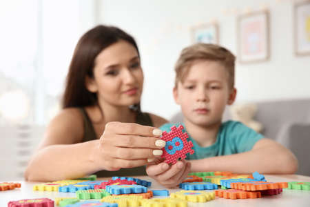 Foto de Young woman and little boy with autistic disorder playing at home, closeup - Imagen libre de derechos