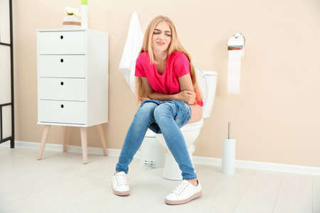 Foto de Young woman suffering from diarrhea on toilet bowl at home - Imagen libre de derechos