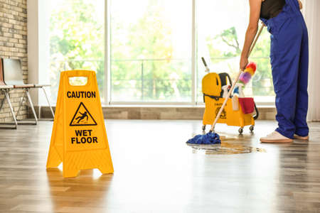 Photo pour Safety sign with phrase Caution wet floor and cleaner indoors. Cleaning service - image libre de droit