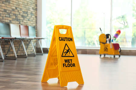 Foto per Safety sign with phrase Caution wet floor, indoors - Immagine Royalty Free