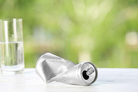 Foto de Crumpled aluminum can on table against blurred background. Metal waste recycling - Imagen libre de derechos