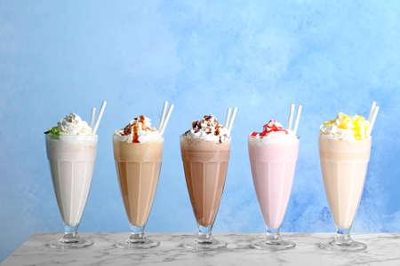 Photo pour Glasses with delicious milk shakes on table - image libre de droit