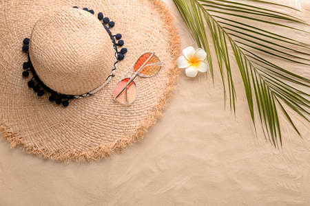 Photo for Flat lay composition with stylish hat, flower and tropical leaf on sand - Royalty Free Image