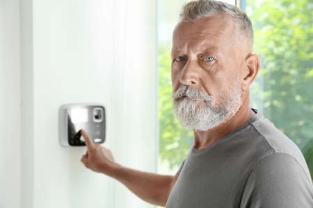 Photo for Mature man entering code on alarm system keypad indoors - Royalty Free Image