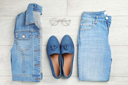 Photo pour Flat lay composition with blue jeans, jacket and shoes on wooden background - image libre de droit