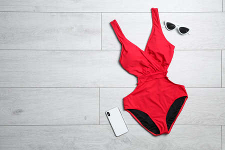 Photo for One-piece swimsuit, sunglasses and smartphone on wooden background - Royalty Free Image
