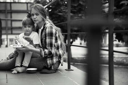 Foto de Poor people eating donated food on street, black and white effect - Imagen libre de derechos
