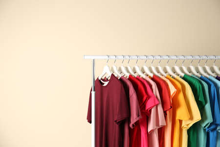 Foto de Many t-shirts hanging in order of rainbow colors on light background - Imagen libre de derechos