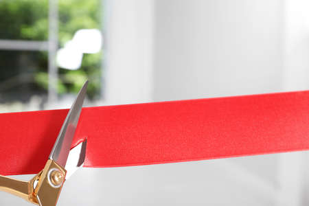 Photo pour Ribbon and scissors on blurred background. Ceremonial red tape cutting - image libre de droit