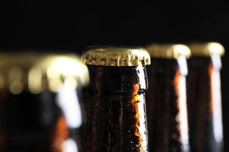 Foto de Many bottles of beer on dark background, closeup view - Imagen libre de derechos