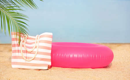 Photo for Colorful inflatable ring and bag on sand. Beach object - Royalty Free Image