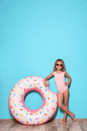 Photo for Cute little girl with bright inflatable ring near color wall - Royalty Free Image