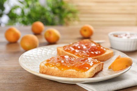 Photo for Bread with tasty apricot jam on plate - Royalty Free Image