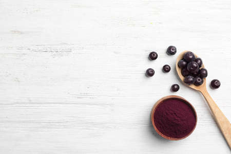 Foto de Bowl of acai powder and fresh berries on light wooden table, flat lay with space for text - Imagen libre de derechos