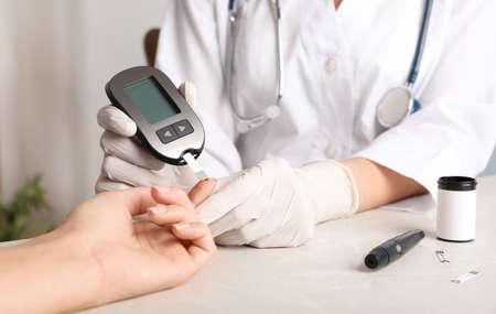 Photo pour Doctor checking blood sugar level with glucometer at table. Diabetes test - image libre de droit