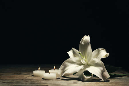 Photo pour Beautiful lily and burning candles on dark background with space for text. Funeral flower - image libre de droit