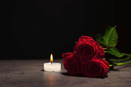 Foto de Beautiful red roses and candle on table against black background. Funeral symbol - Imagen libre de derechos