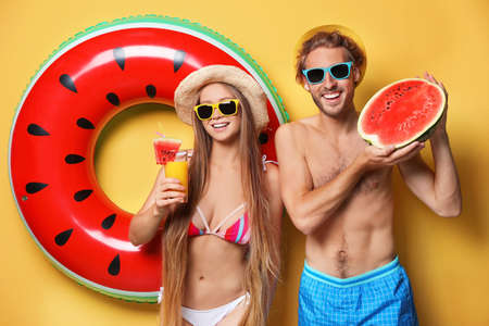 Photo for Young couple in beachwear with inflatable ring and watermelon on color background - Royalty Free Image