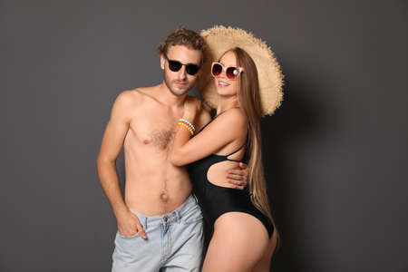 Photo for Happy young couple in beachwear on dark background - Royalty Free Image