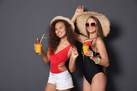 Photo for Beautiful young women in beachwear with cocktails on dark background - Royalty Free Image