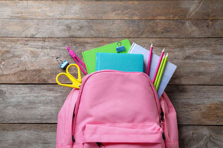 Photo for Flat lay composition with backpack and school stationery on wooden background - Royalty Free Image