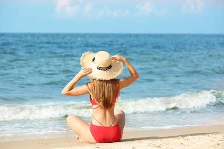 Photo for Attractive young woman in beautiful one-piece swimsuit on beach - Royalty Free Image