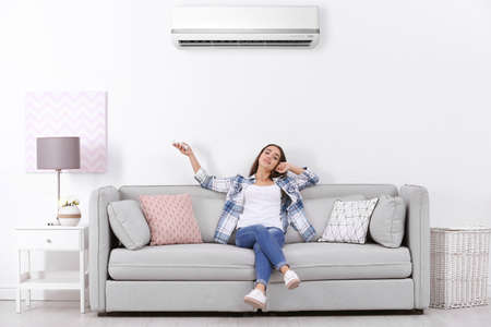 Photo pour Young woman operating air conditioner while sitting on sofa at home - image libre de droit