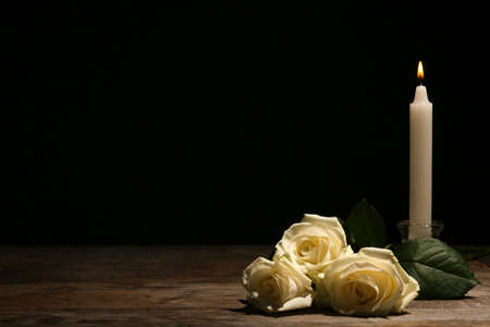 Photo pour Beautiful white roses and candle on table against black background. Funeral symbol - image libre de droit