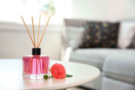 Photo pour Aromatic reed parfume and rose on table indoors - image libre de droit