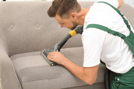 Photo pour Male janitor removing dirt from sofa with upholstery cleaner indoors - image libre de droit