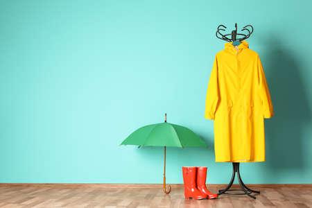 Foto für Umbrella, rain coat and boots near color wall with space for design - Lizenzfreies Bild