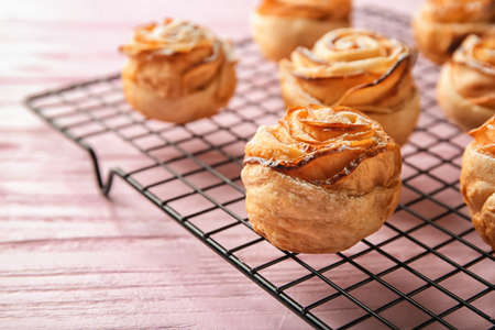 Photo pour Cooling rack with apple roses from puff pastry on color wooden background, closeup - image libre de droit