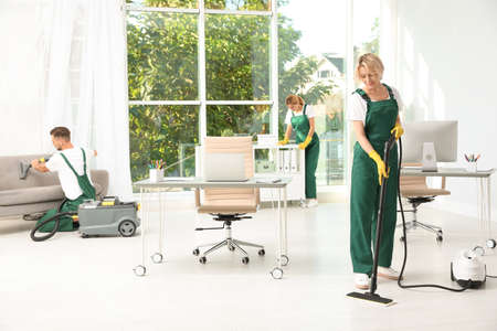 Foto de Team of janitors in uniform cleaning office - Imagen libre de derechos