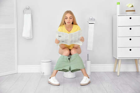 Foto de Young woman reading newspaper while sitting on toilet bowl at home - Imagen libre de derechos