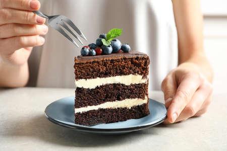 Photo pour Woman with slice of chocolate sponge berry cake at table, closeup - image libre de droit