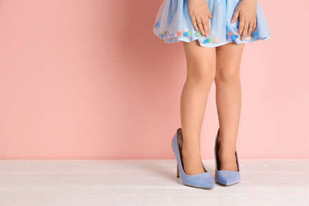 Foto de Little girl in oversized shoes near color wall with space for text, closeup on legs - Imagen libre de derechos