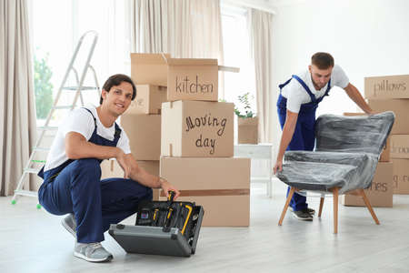 Foto für Male movers with instruments and armchair in new house - Lizenzfreies Bild