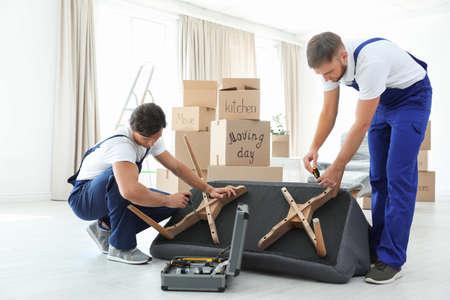 Photo pour Male movers assembling sofa in new house - image libre de droit