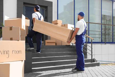 Foto de Male movers carrying shelving unit into new house - Imagen libre de derechos