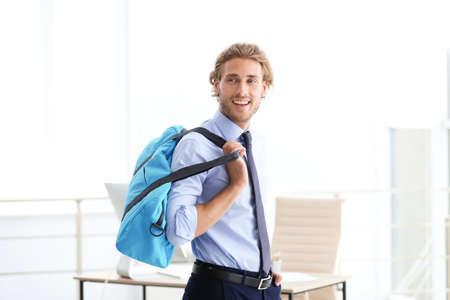 Foto de Young handsome businessman holding fitness bag in office. Gym after work - Imagen libre de derechos